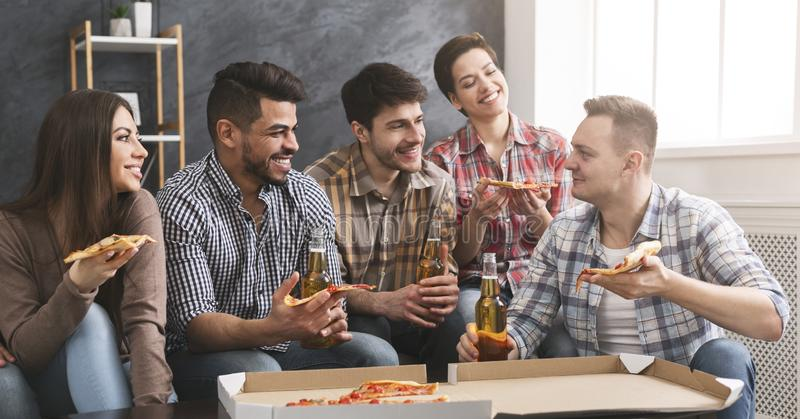 Home party. Group of friends eating pizza, drinking beer and talking stock image