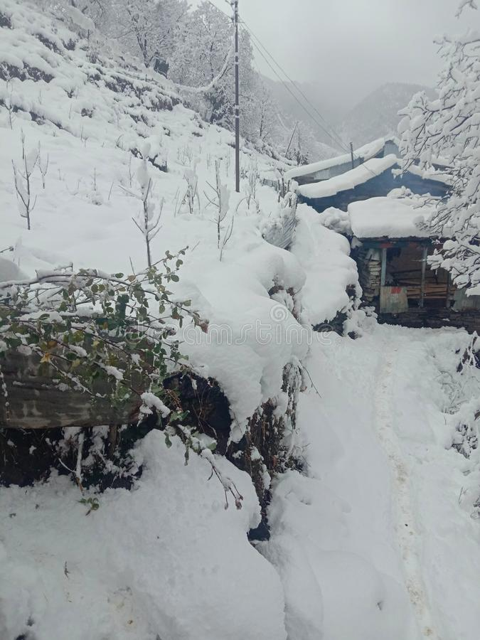 It is the home of a poor person in India who is snowed. There is snow around the house, it is difficult to get out. It is the home of a poor in India who is stock photos