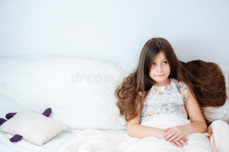 Home portrait of a little girl with long hair sitting on a couch covered with a blanket stock image