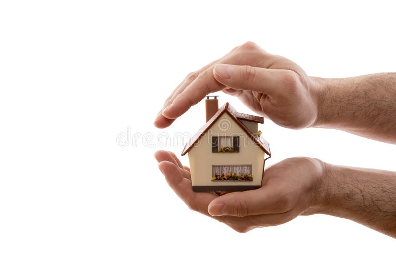 Home protection. Small house covered by hands isolated on white background. With clipping path stock images