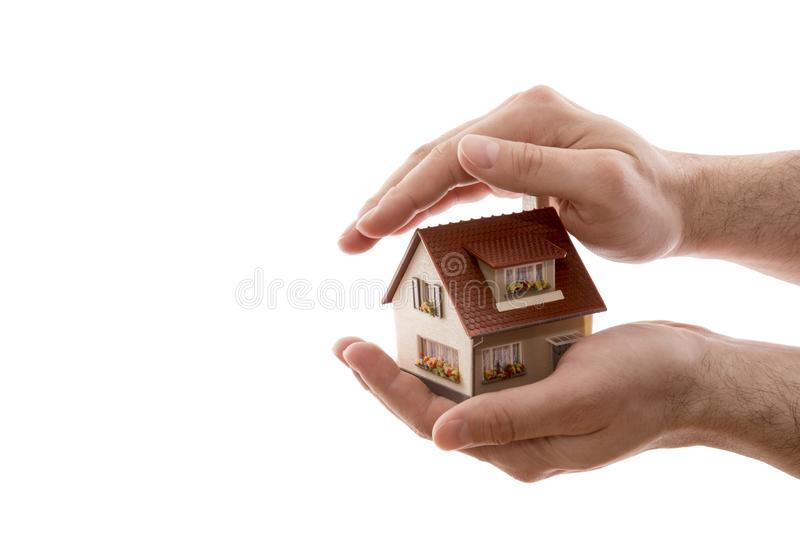 Home protection. Small house covered by hands isolated on white background. With clipping path stock photos