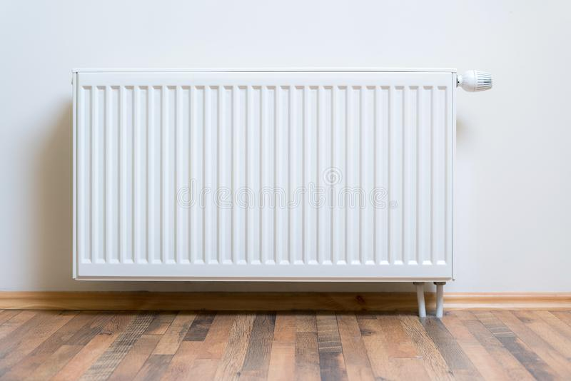 Home radiator heater on the white wall on wooden hardwood floor. Adjustable warming equipment for apartment and home.  royalty free stock image