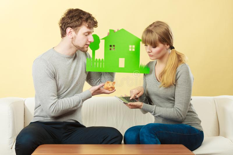 Worried couple with house. Home real estate credit mortgage concept. Worried couple with house. Young men and women holding building cutout and calculator stock photos