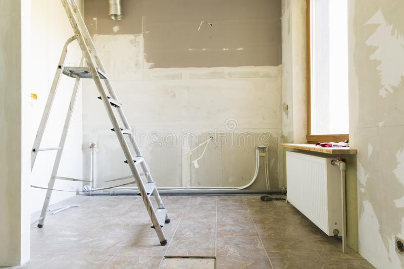Home renovation concept. Kitchen in process of repair and renovation. Ladder and construction tools royalty free stock photos