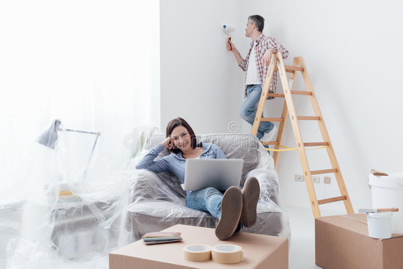 Home renovation. Happy couple doing home renovations, the men is painting the room and the women is relaxing on the armchair and connecting with a laptop royalty free stock photos
