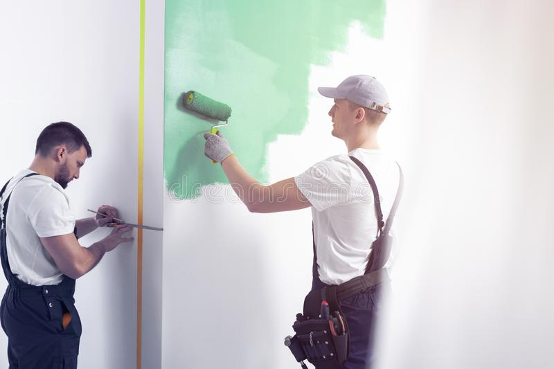 Home renovation worker with a tool belt painting a wall green wi. Th a roller and another professional in dungarees taking measurements royalty free stock photos
