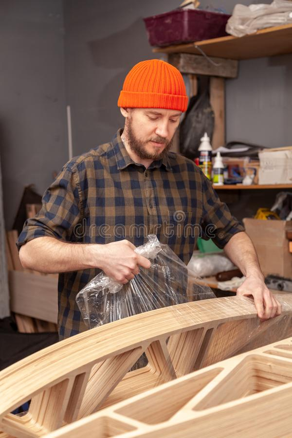 Home repair concepts. Close up. Carpenter-maker packs the finished product with a protective film for transporting the wooden shelf on the working table in the royalty free stock photos