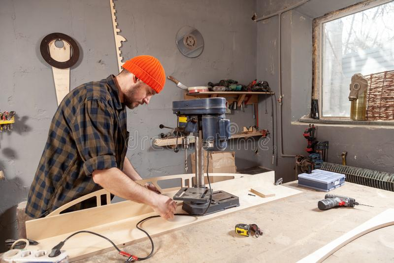 Home repair concepts. Close up of carpenter in work clothes carving a wooden on an drill. Manual job DIY inspiration improvement job fix shop helmet joinery stock image