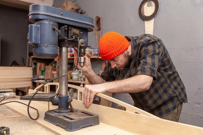 Home repair concepts. Close up. Handicraft Carpentry. Cabinet-maker hands drilling a wooden plank using drilling machine on the working table in the workshop stock photos