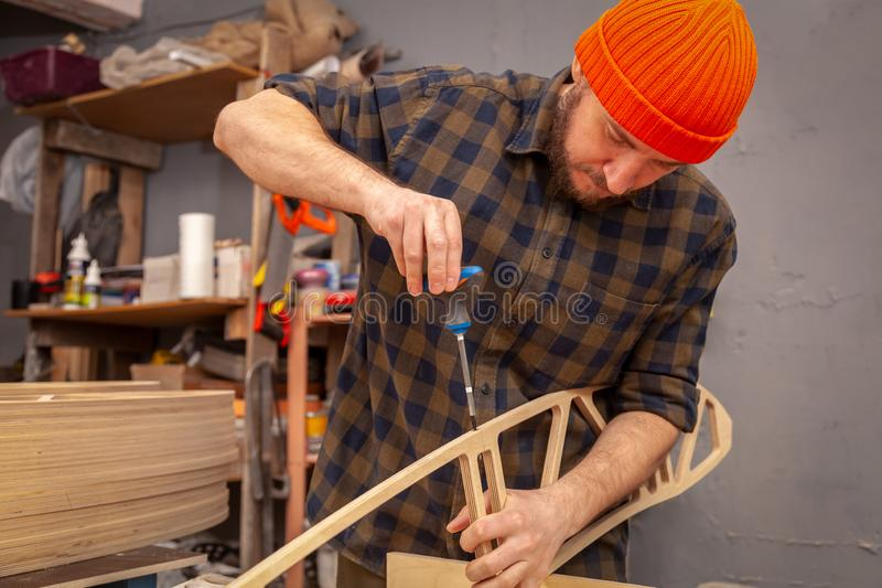 Construction Worker. Home repair concepts, close up. Handicraft Carpentry. Cabinet-maker hands drilling a wooden plank using turn-screw on the working table in royalty free stock photos