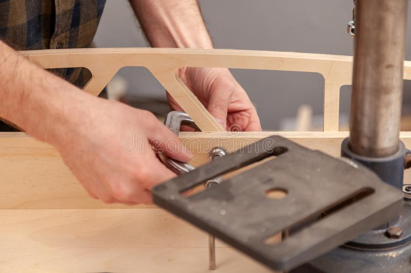 Construction Worker. Home repair concepts, close up. Handicraft Carpentry. Cabinet-maker hands tightens the nuts  on wooden board with a clamp on the working stock photo