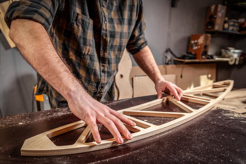 Home repair concepts. Close up of a young man carpenter builder equals a wooden bar with a milling machine in the workshop, in the background wooden boards stock photography