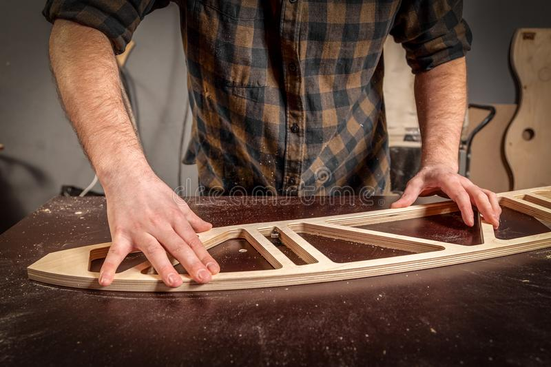 Home repair concepts. Close up of a young man carpenter builder equals a wooden bar with a milling machine in the workshop, in the background wooden boards royalty free stock photos