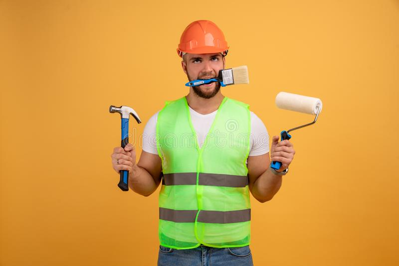 Home repair male worker busy with house renovation, holds building equipment, has sad expression, wears casual working clothes. stock images