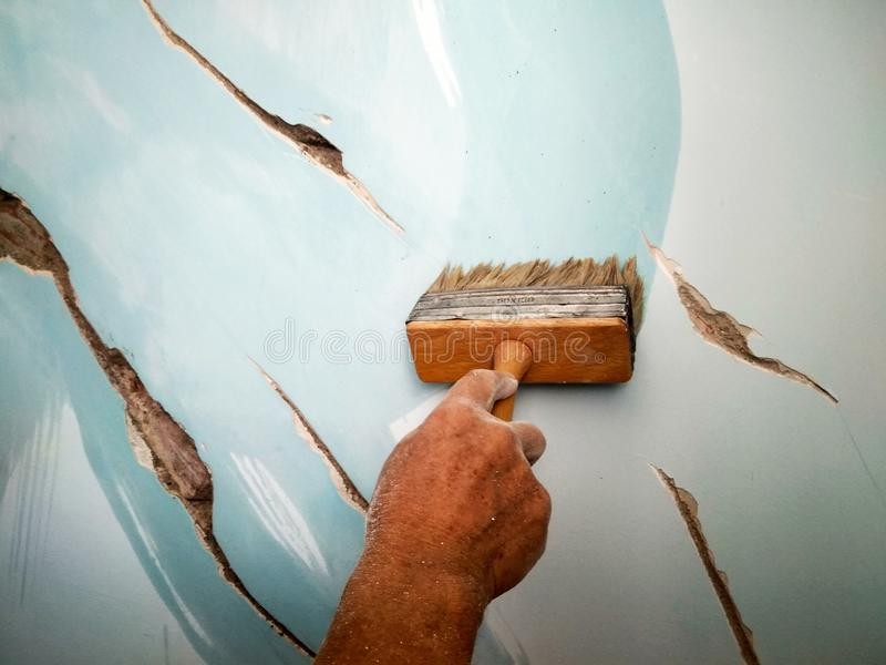 Home repair, a man brushes the cracks in the wall before puttying. With a brush royalty free stock photo