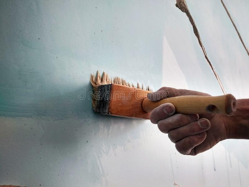 Home repair, a man brushes the cracks in the wall before puttying. With a brush royalty free stock photos