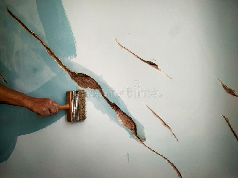 Home repair, a man brushes the cracks in the wall before puttying. With a brush royalty free stock images