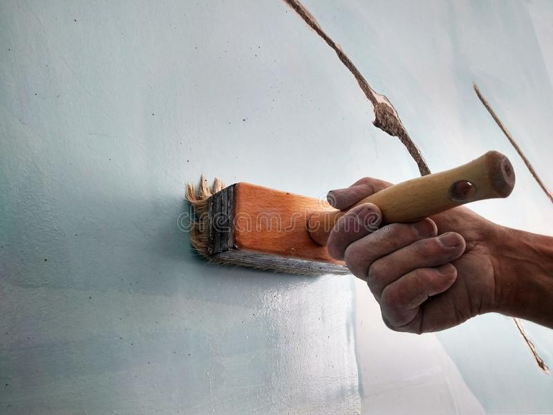 Home repair, a man brushes the cracks in the wall before puttying. With a brush stock photography