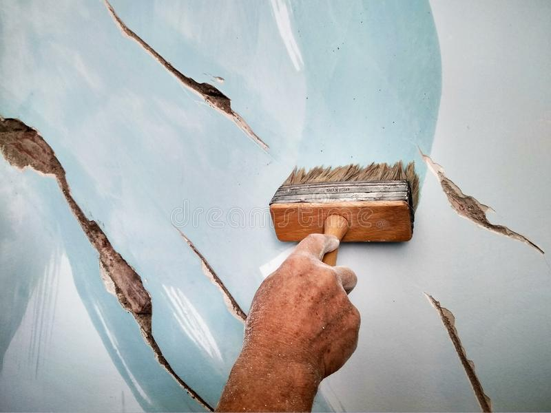 Home repair, a man brushes the cracks in the wall before puttying. With a brush stock photo