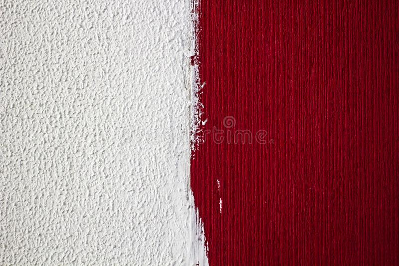 Home repairs. Wall with different textures, one half painted white, the other red royalty free stock photo