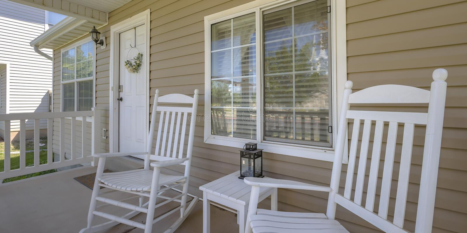 Home with rocking chairs and table on front porch royalty free stock photo