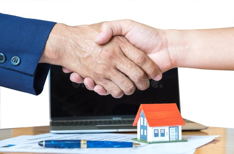 Home salesman shakes hands,Pen and model house on house plan. Home salesman shakes hands,Pen and model house on house plan,Model house with red roof and blue stock photos