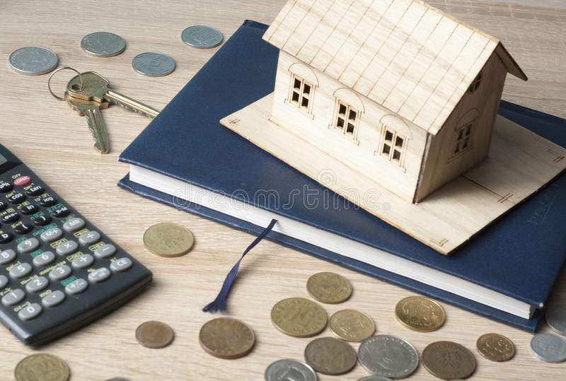 Home savings, budget concept. Model house, notepad, keys, calculator and coins on wooden office table. stock photo