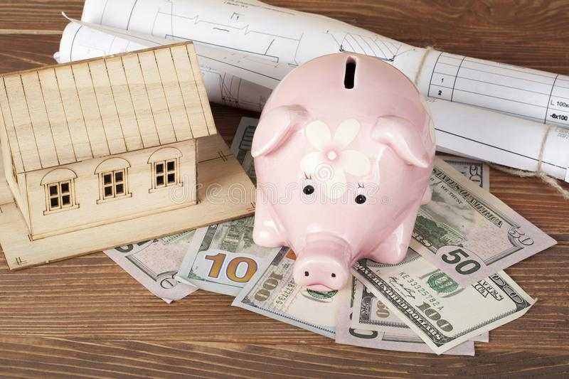 Home savings, budget concept. Model house, piggy bank,money on wooden office table. Home savings, budget concept. Model house, piggy bank and money on wooden stock image