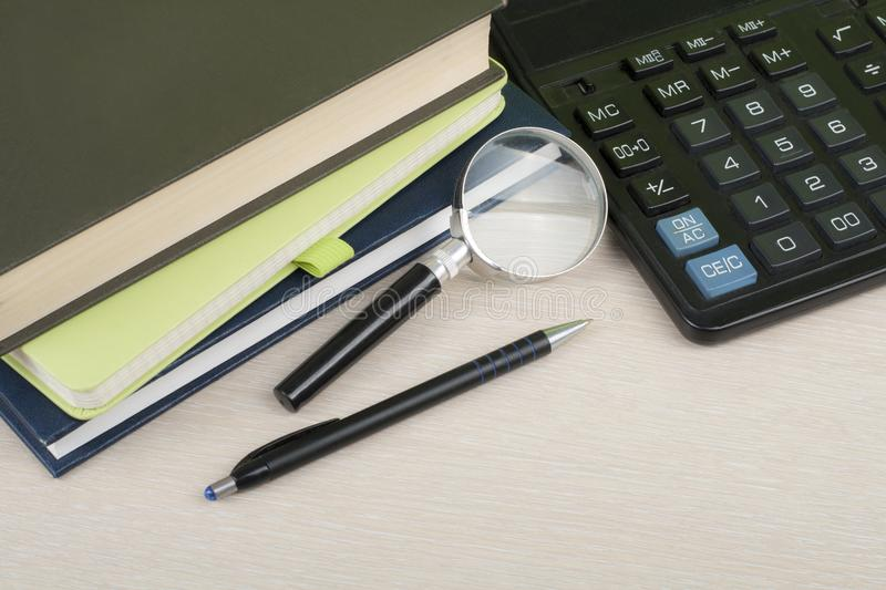 Home savings, budget concept. Notepad, pen, calculator,magnifying glass on wooden office desk table. stock photography