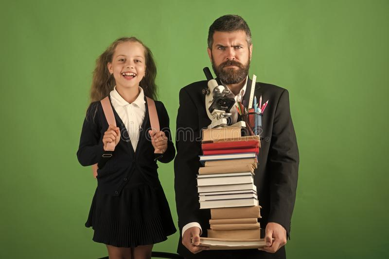 Home schooling and back to school concept Kid and dad hold pile of books with school supplies. Girl and bearded man in. Suit. Father and schoolgirl with mad and stock photo