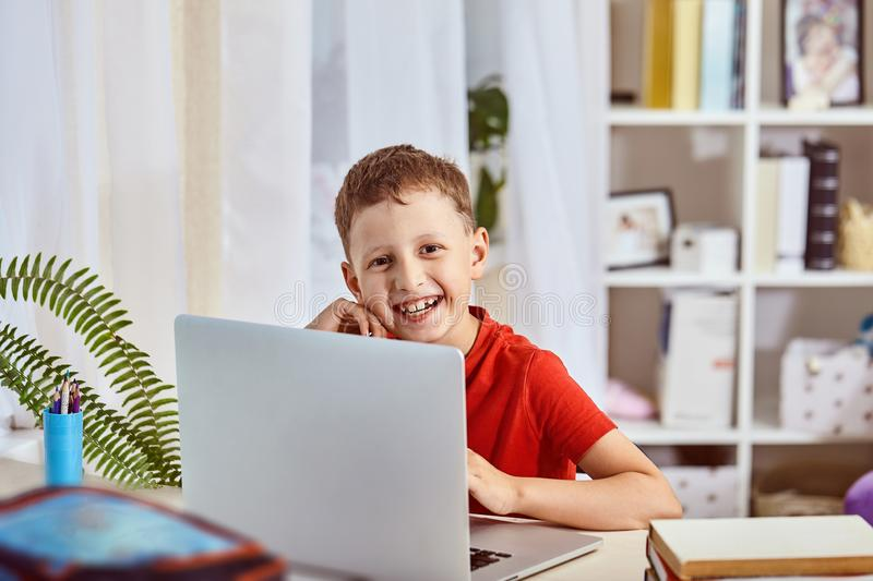 Home schooling, search and study, new knowledge.happy child at the table with the computer.little boy student sitting at a table royalty free stock images