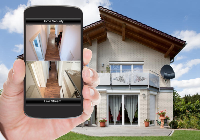 Home security. Close-up Of Person Hand Holding Mobile Phone With Home Security System royalty free stock photography