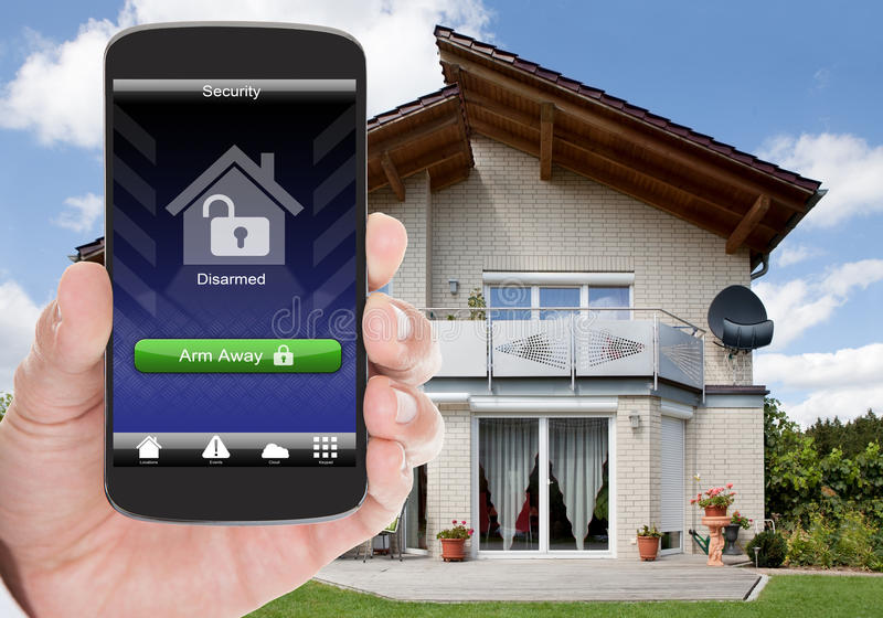 Home security. Close-up Of Person Hand Holding Mobile Phone With Home Security System royalty free stock photo