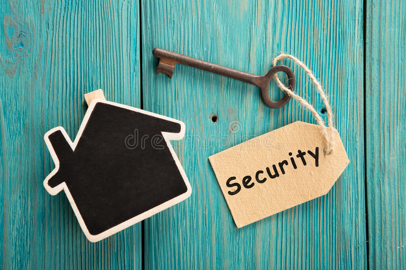 Home security concept. Little house and old key with tag stock photo