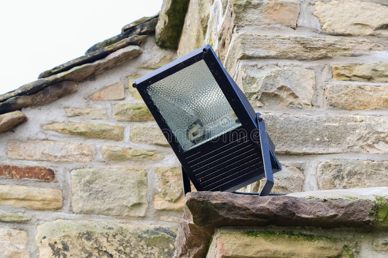 Home security light mounted on the corner of a rural stone cottage royalty free stock image