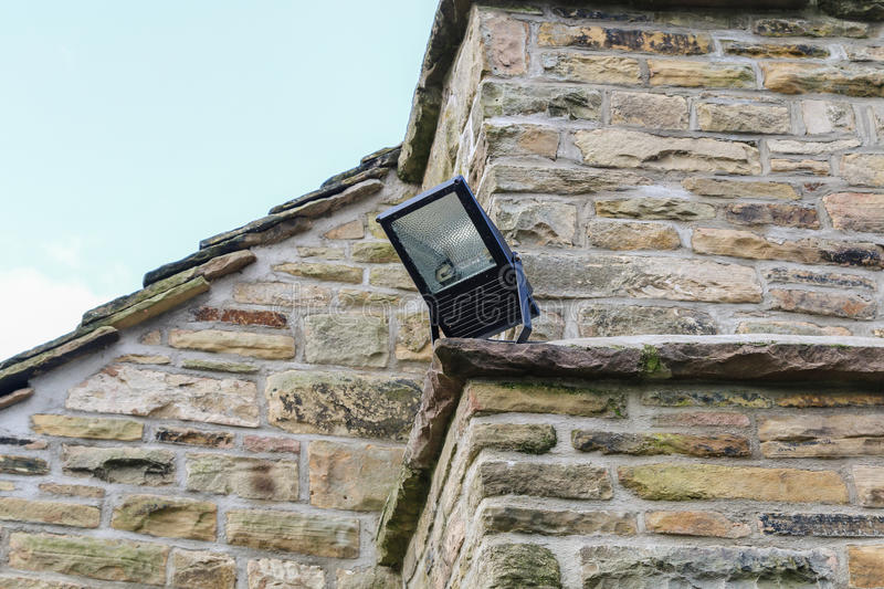 Home security light mounted on the corner of a rural stone cottage. stock images