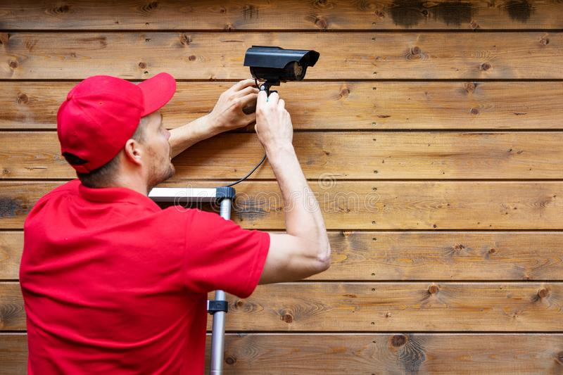 Home security - man installing outdoor surveillance camera on wooden wall copy space royalty free stock photo