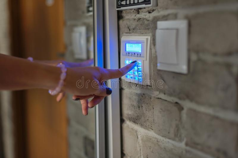 Home security system. Woman entering password on home alarm keypad royalty free stock images