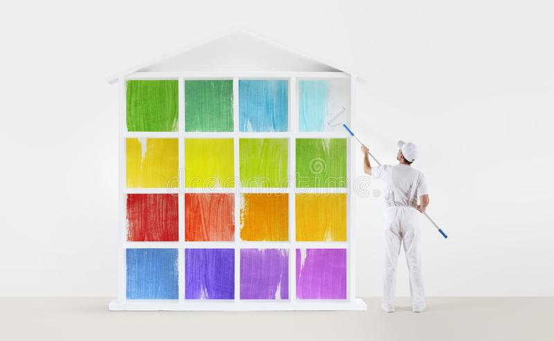 Home service concept. painter man with paint roller, painting a royalty free stock image