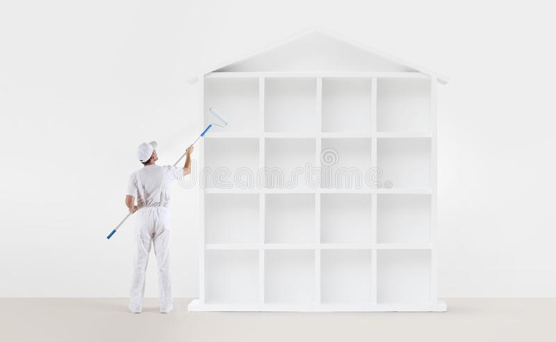 Home service concept. painter man with paint roller, painting a royalty free stock photos