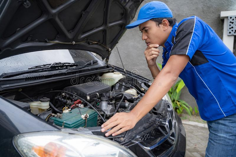 Mechanic doing some inspection on car`s engine. Home service mechanic doing some inspection on car`s engine stock photography