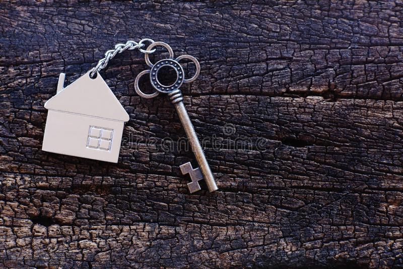 Home shape keyring with antique key on old wooden table. Welcome to new home, home sweet home concept. Copy space stock images