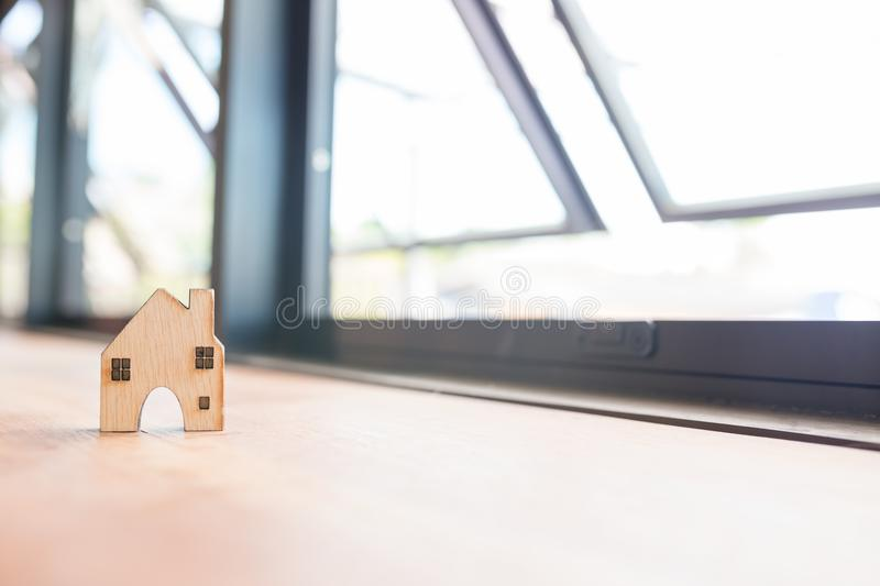 Home shape wood besides window. Concepts for real estate and business stock images
