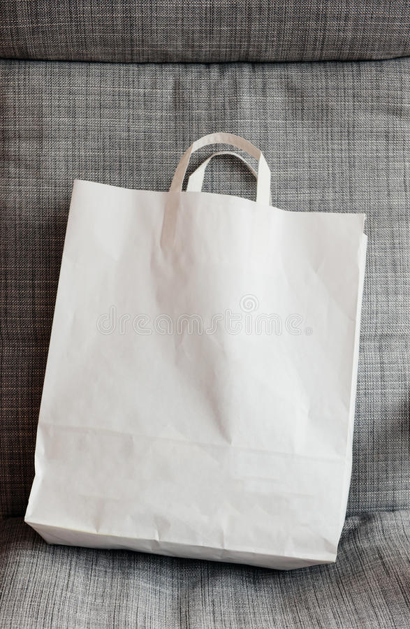 White paper bag on armchair. Home shopping white fashion bag with logo copy space on armchair royalty free stock image