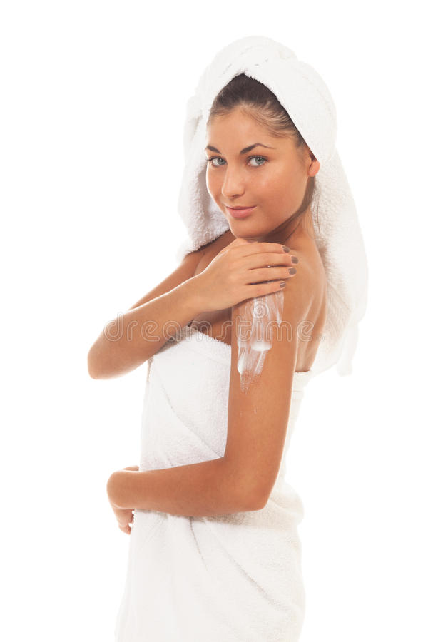 Home spa ritual. Girl applying cream on isolated white royalty free stock photography