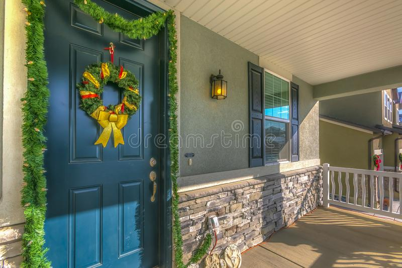 Home with a sunlit porch and front door decorated with wreath and garland. The scenic mountain and vibrant blue sky are reflected on the sliding glass window stock photography