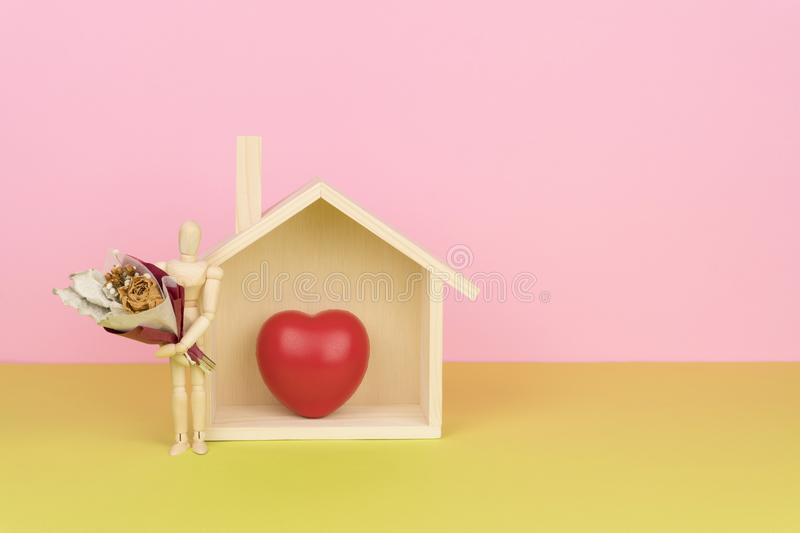 wood figure holding a bouquet of dried flower, standing beside the wooden home model stock image