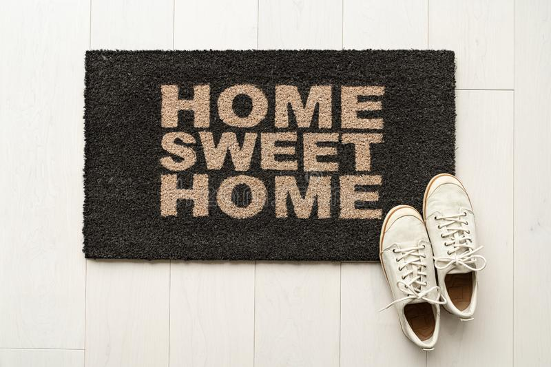 Home sweet home door mat at house entrance with women`s sneakers of woman that has just arrived moved in. New condo stock image