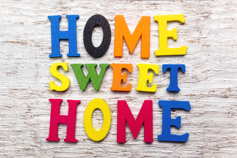 'Home Sweet Home' message wooden sign. On white wooden background stock photos
