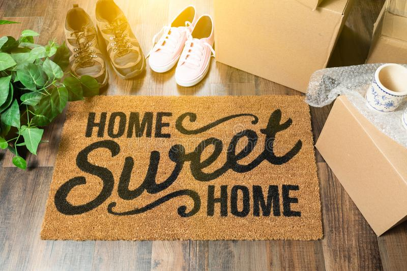 Home Sweet Home Welcome Mat, Moving Boxes, Women and Male Shoes. And Plant on Hard Wood Floors royalty free stock images